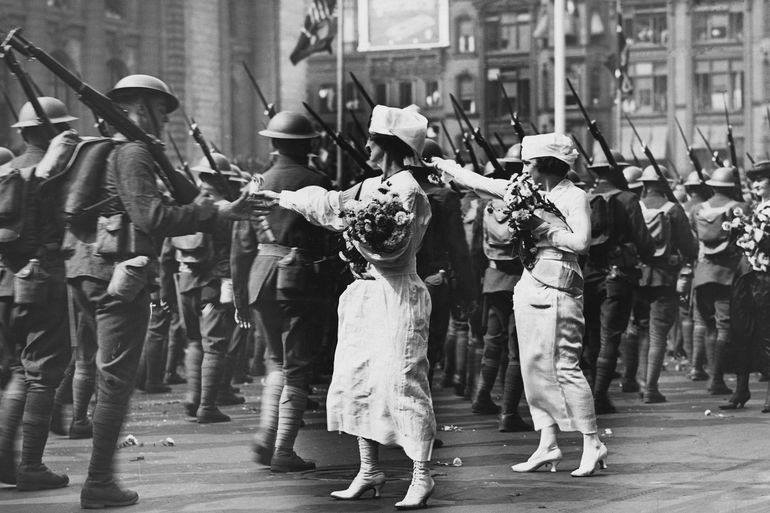 English troops are handed flowers while marching through London on the way to war.